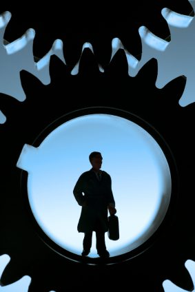 Worker silhouetted through gears