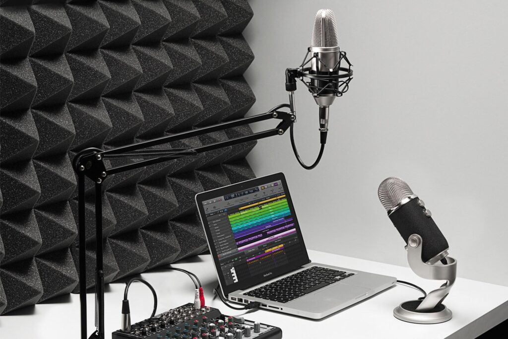 Laptop computer set up with two microphones and an audio mixer for posdcasting production